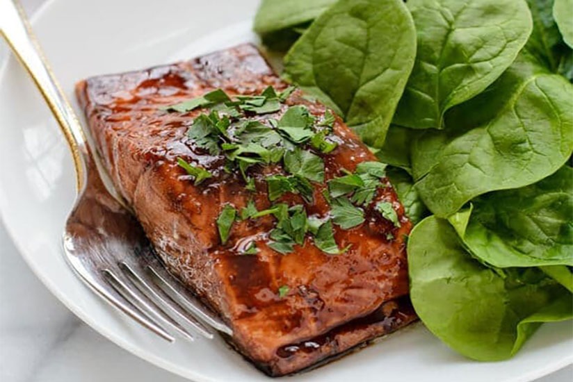 Balsamic glazed salmon garnished with chopped parsley on plate