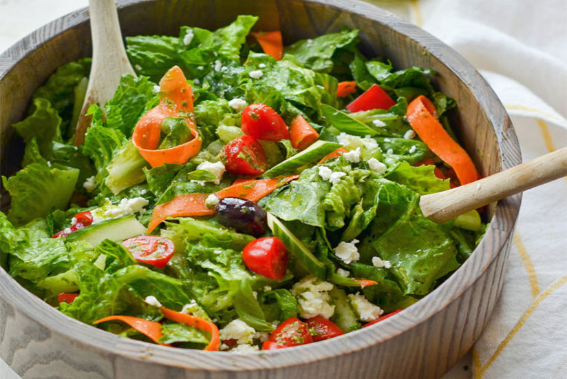 Italian salad in wood bowl with wood salad spoon and fork