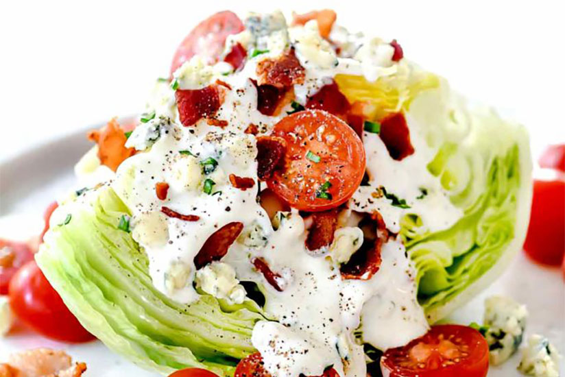 Blue cheese wedge salad with sliced tomatoes and bacon on plate