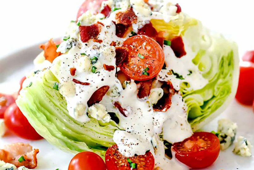 Iceberg lettuce topped with blue cheese and tomatoes on plate