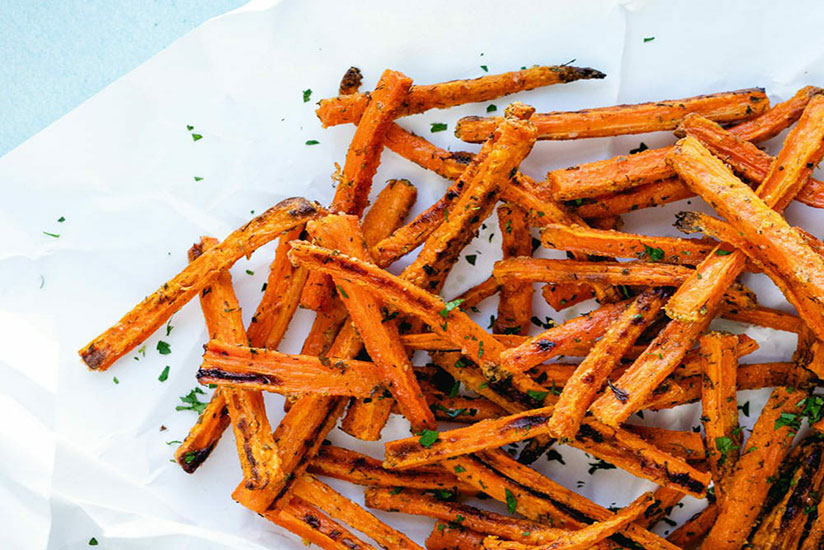 Roasted carrot fries sprinkled with herbs on top of paper on counter