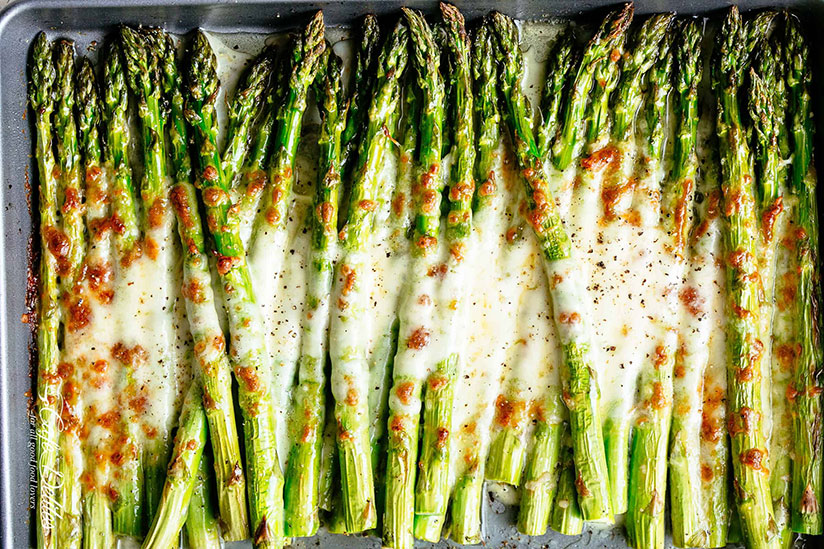 Garlic roasted asparagus spears topped with melted cheese on tray