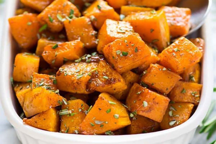 Roasted butternut squash in white dish on marble counter