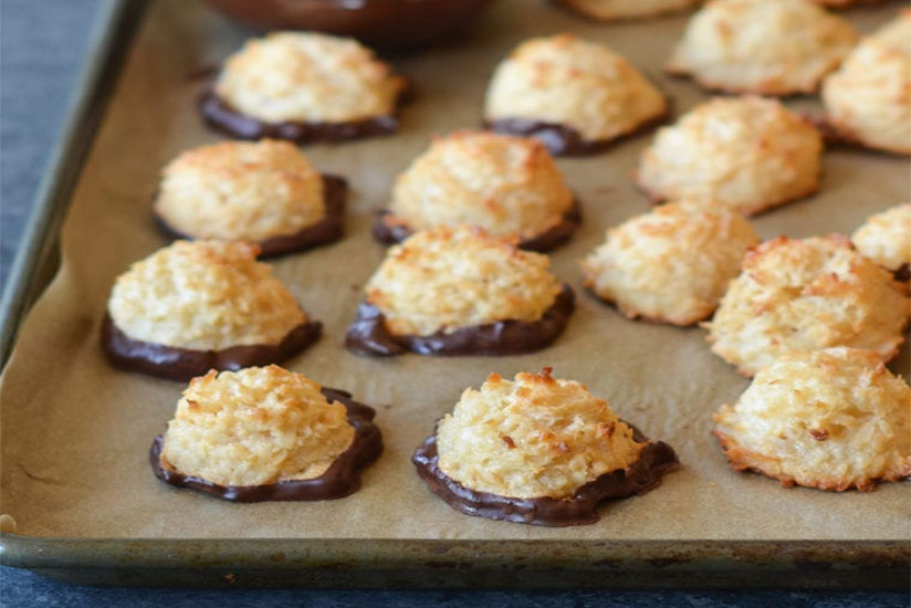 Coconut macarons dipped in chocolate on tray on marble counter