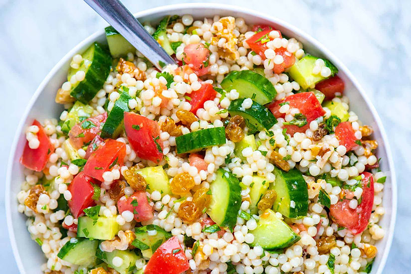 Lemon and herb couscous salad in white bowl on marble counter