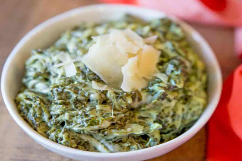 Creamed spinach topped with cheese shavings in white bowl on counter