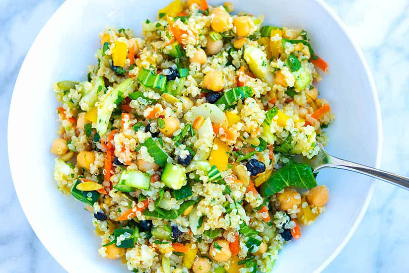 Quinoa salad with beans and cucumber slices in white bowl on counter