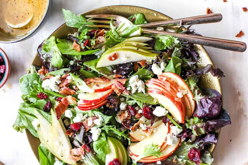 Harvest fall salad on gold plate with forks on white counter