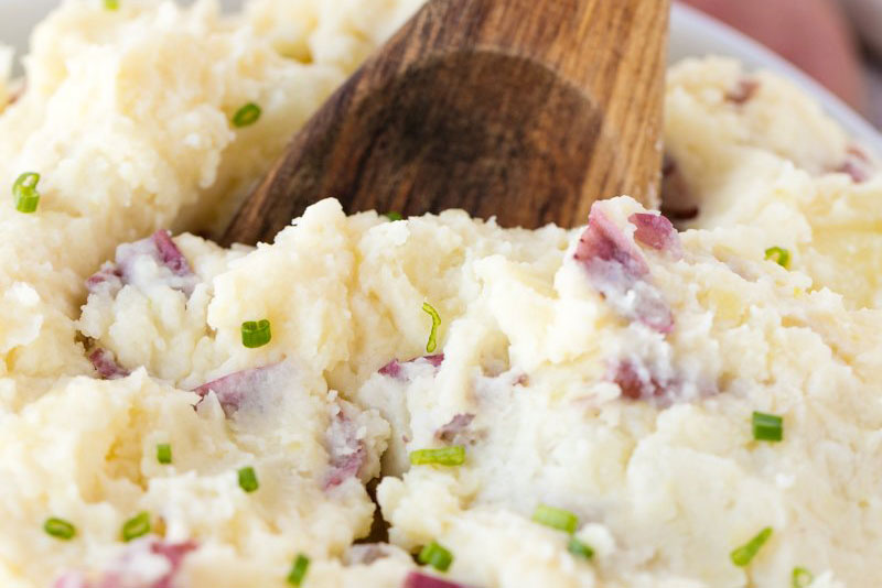 Garlic mashed Yukon potatoes with sliced green onions in bowl
