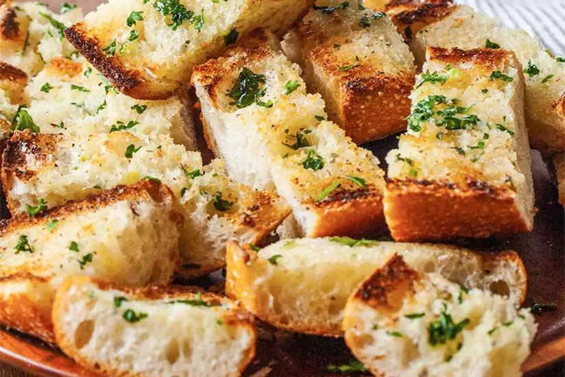 Sliced garlic bread sprinkled with herbs on wood plate on counter
