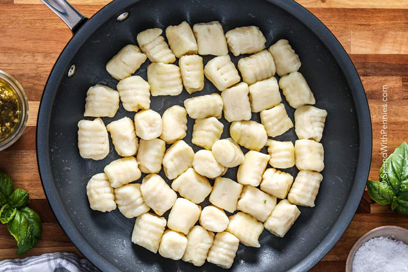 Homemade gnocchi on black pan on wood counter