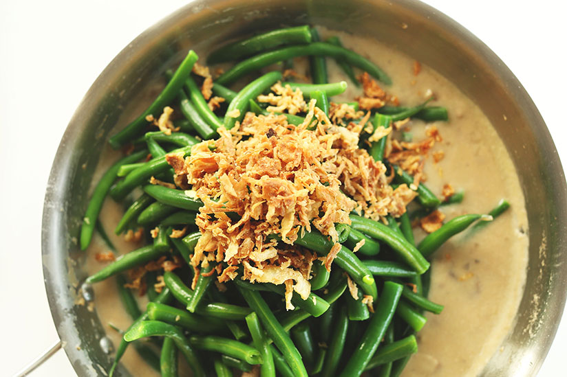 Green beans topped with crunchy onions on pan on white background