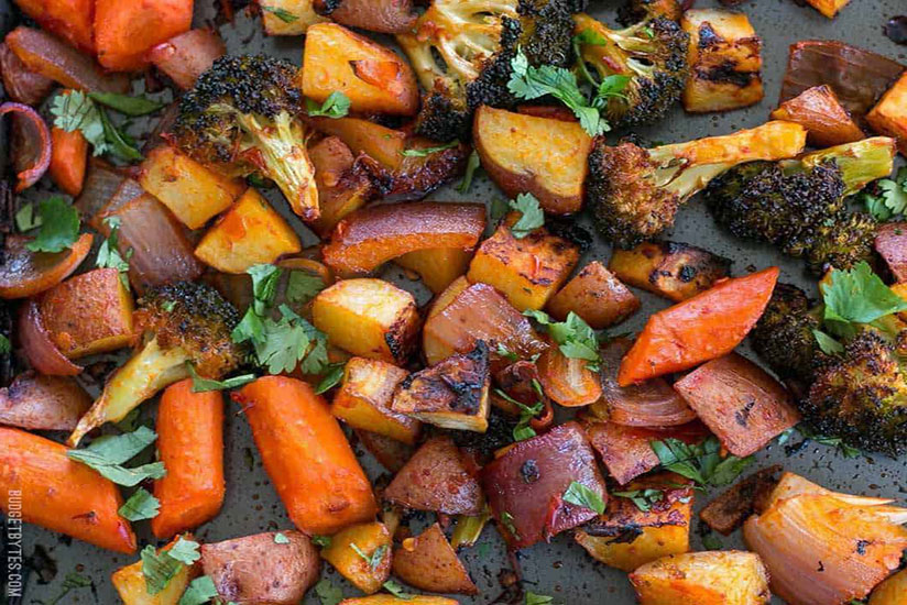 Chopped roasted vegetables with harissa paste on metal tray