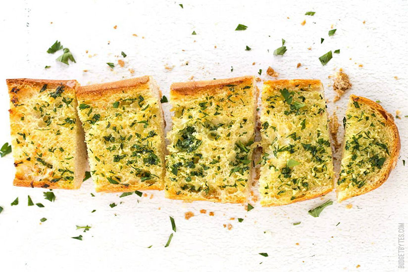 Sliced homemade garlic bread topped with chopped parsley on counter