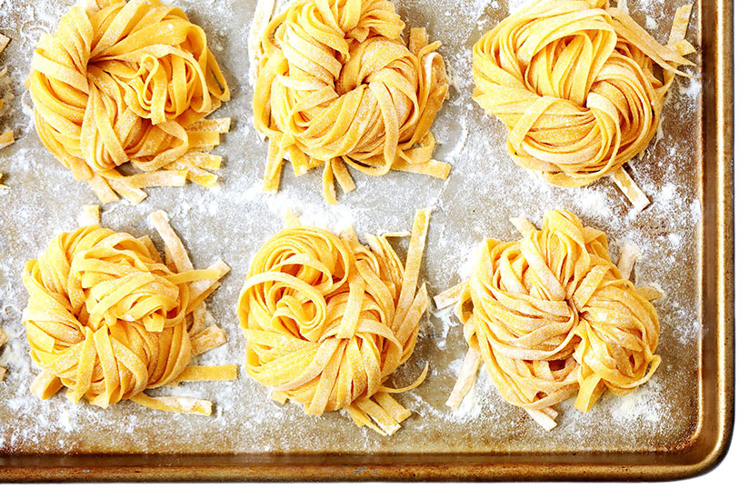 Six balls of homemade noodles sprinkled with flour on tray