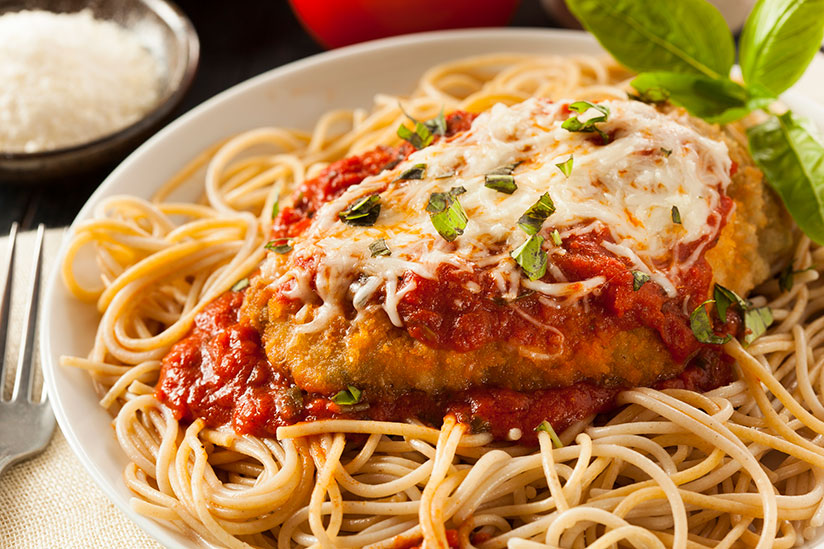 Italian chicken parmesan on top of noodles on white plate