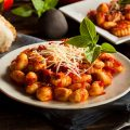 Gnocchi with red sauce and cheese on plate
