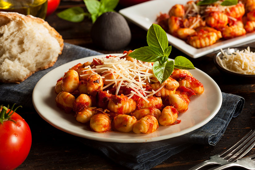 Italian gnocchi topped with shredded cheese on white plate