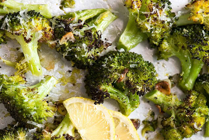 Roasted broccolis sprinkled with cheese beside lemon slice on tray