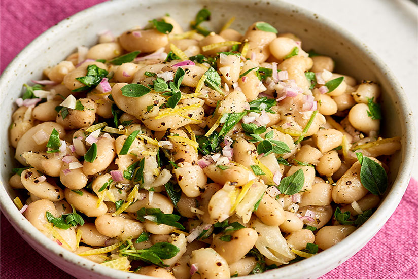 Marinated white beans sprinkled with black pepper in bowl on counter