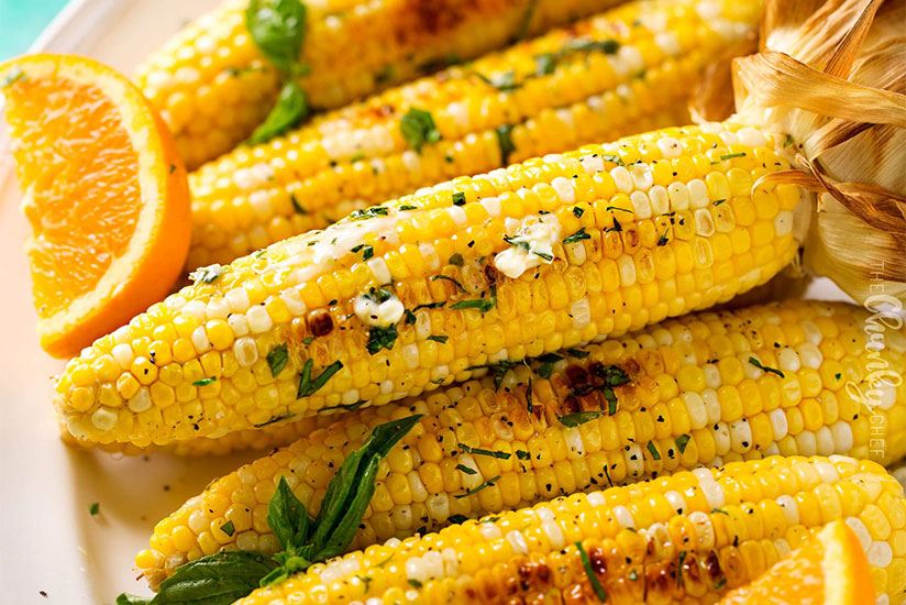 Pile of oven roasted corn on the cob sprinkled with herbs on plate