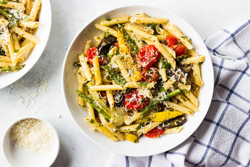 Pasta primavera with roasted vegetables topped with grated cheese on plate