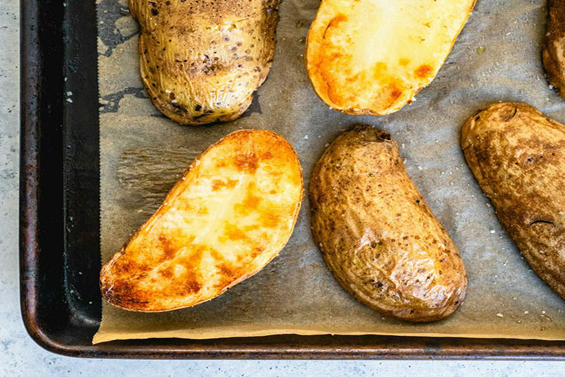 Six halved baked potatoes with two turned over on tray on counter