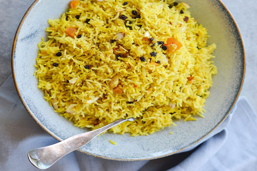 Basmati rice pilaf in blue bowl with spoon on counter