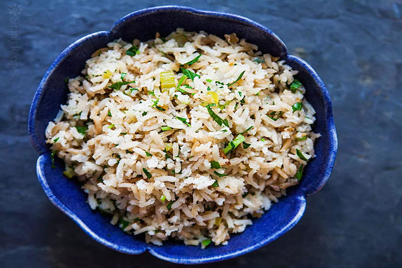Rice pilaf garnished with chopped green onions in blue bowl on counter