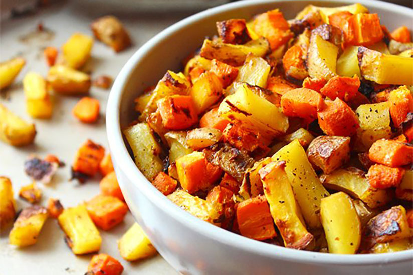 Roasted potatoes and carrots in white bowl on tray