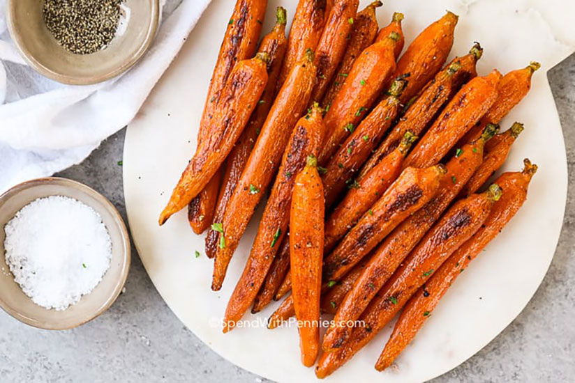 Roasted carrots on plate beside bowl of salt and pepper on counter