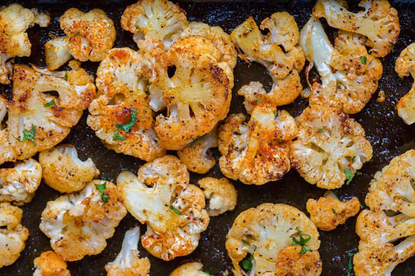Sliced oven roasted cauliflowers sprinkled with herbs on tray