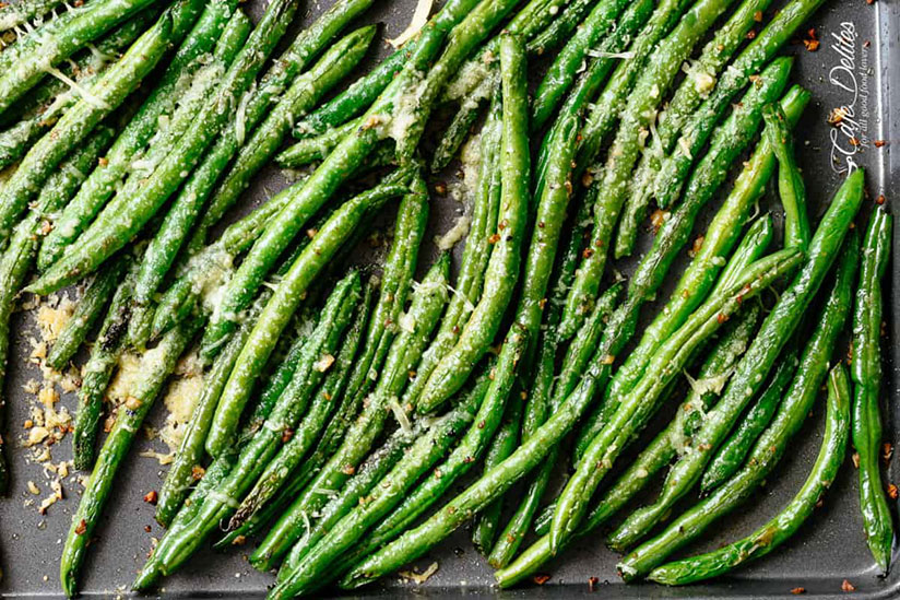 Roasted green beans topped with melted parmesan cheese on tray