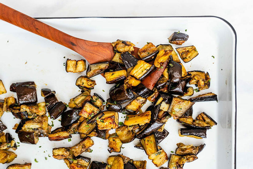 Chopped roasted eggplants in white dish with wood spoon on counter