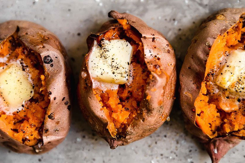 Three baked sweet potatoes topped with slice of butter on counter