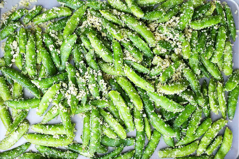 Garlic sugar snap peas sprinkled with parmesan cheese on tray