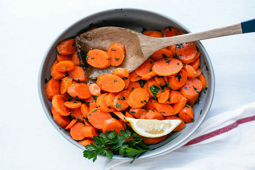 Steamed carrots garnished with chopped parsley in bowl on counter