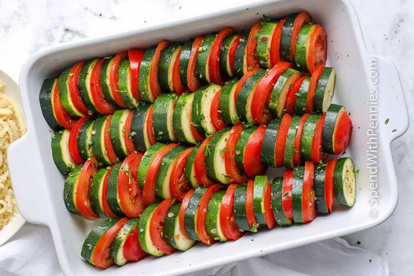 Sliced zucchinis layered with tomato slices in white casserole dish on counter