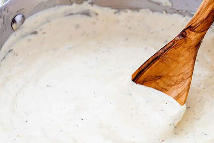 Homemade creamy alfredo sauce cooking in sauce pan with wood spoon