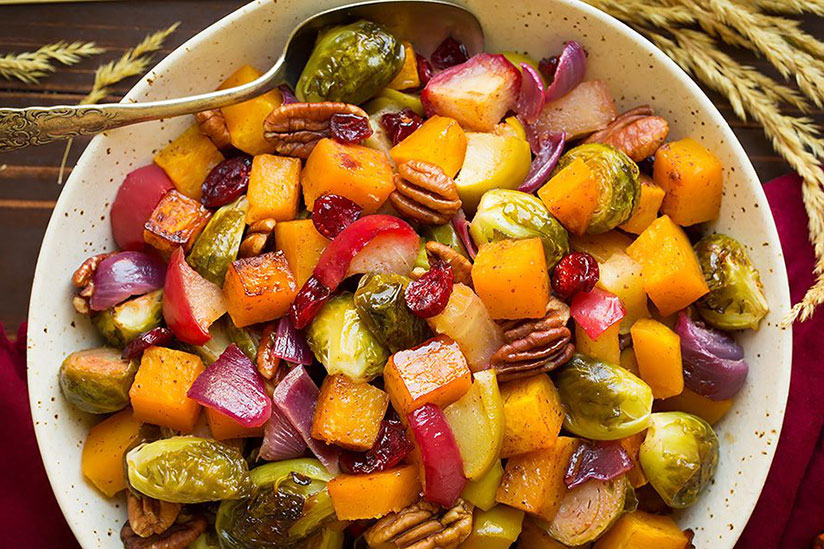 Autumn roasted veggies with apples and pecans on white plate
