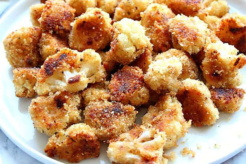 Breaded garlic parmesan cauliflowers on white plate on counter
