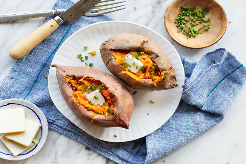 Baked sweet potatoes topped with butter and green onions on plate