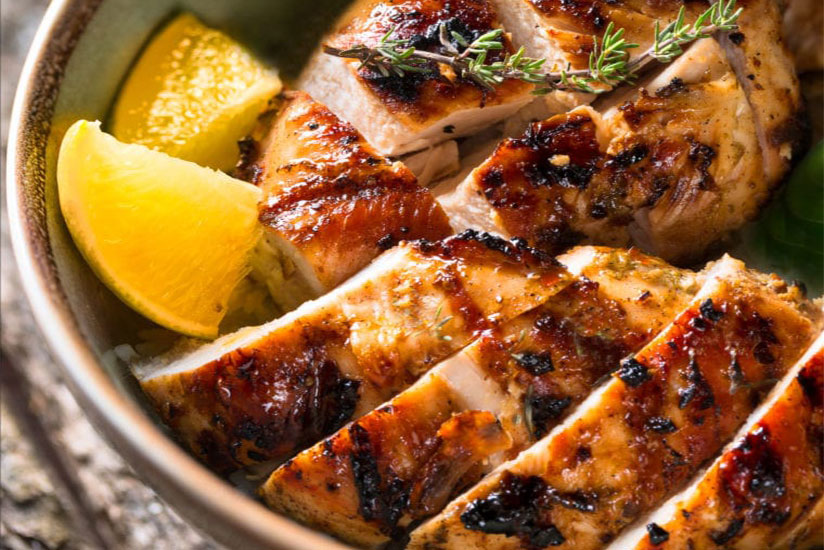 Sliced grilled chicken in bowl with lemon slices on counter