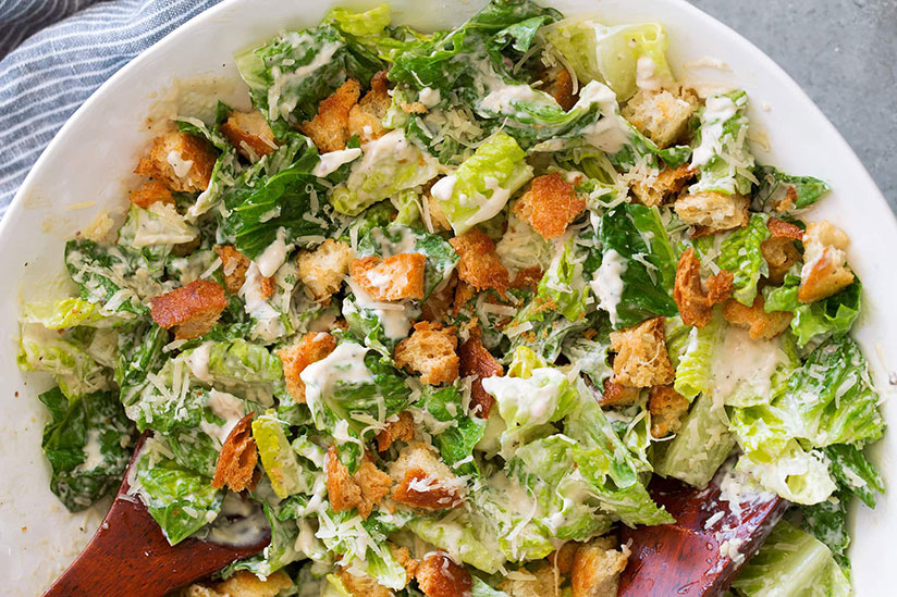 Caesar salad with homemade dressing on white plate on counter