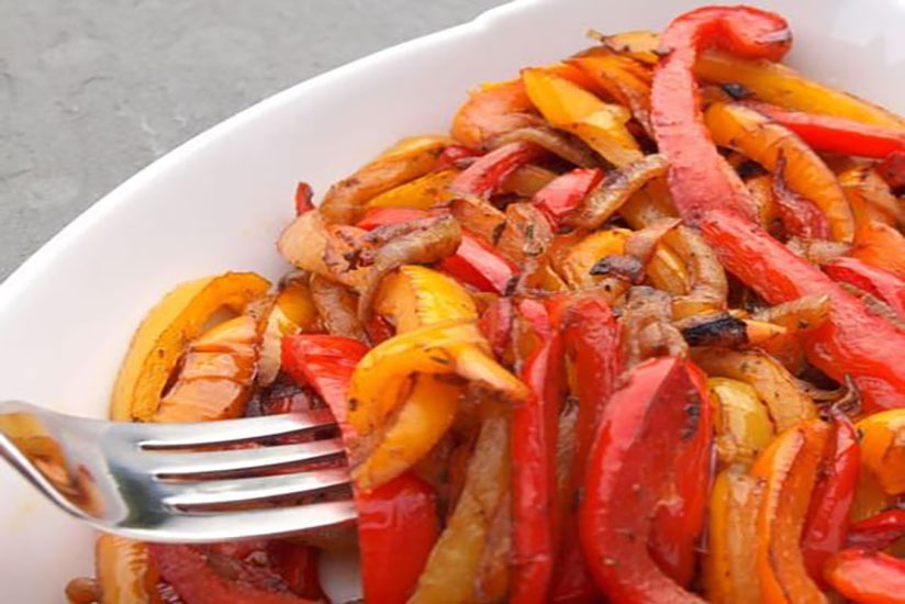 Caramelized onions and red and orange bell peppers on white plate with fork