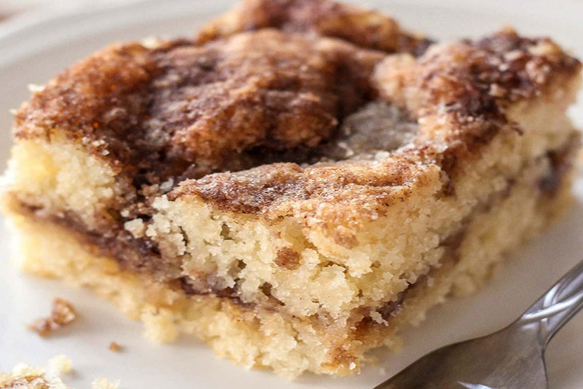 Square slice of coffee cake on white plate with fork