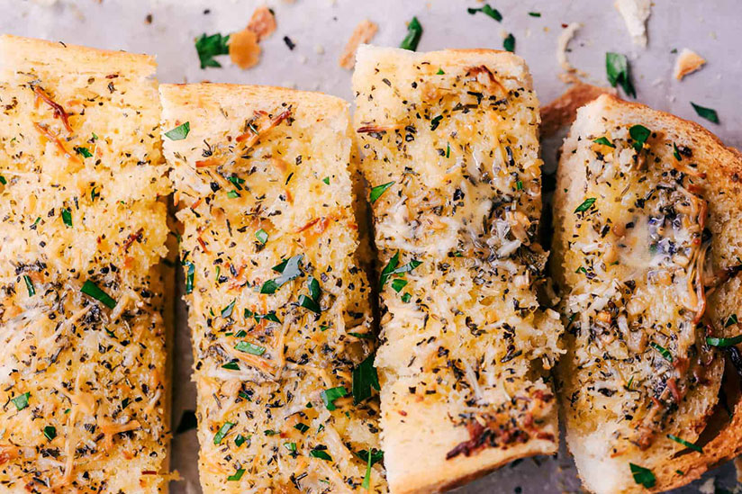 Sliced garlic bread sprinkled with garlic and herbs on counter