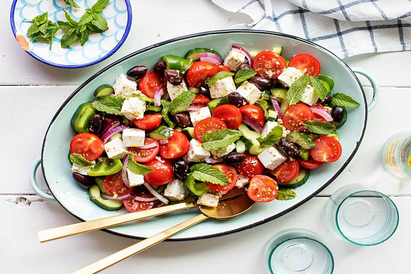 Greek salad with cubed feta cheese and mint leaves in blue dish