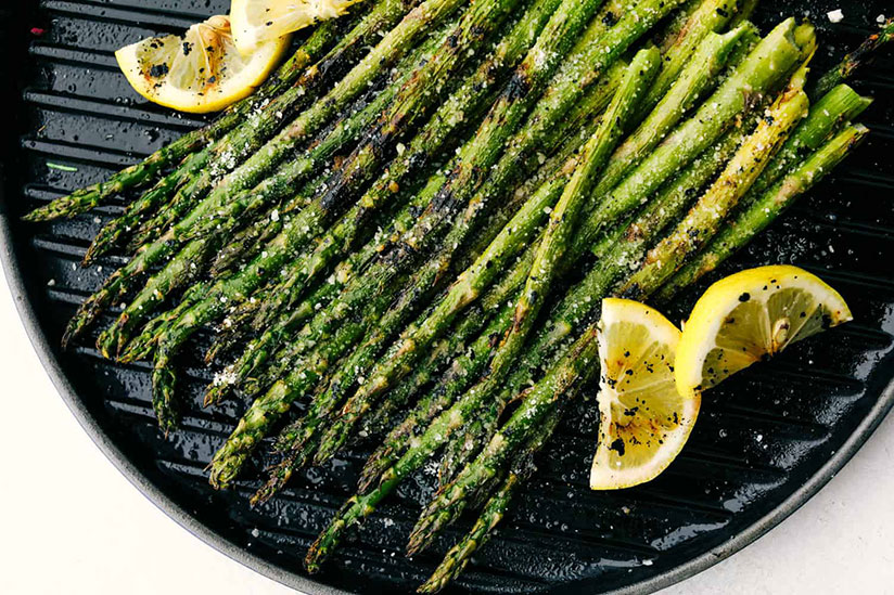 Grilled asparagus stalks on grill pan with lemon slices on counter