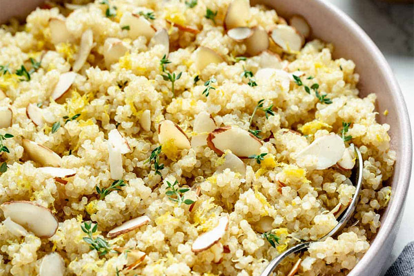 Lemon quinoa topped with sliced almonds in white bowl with spoon
